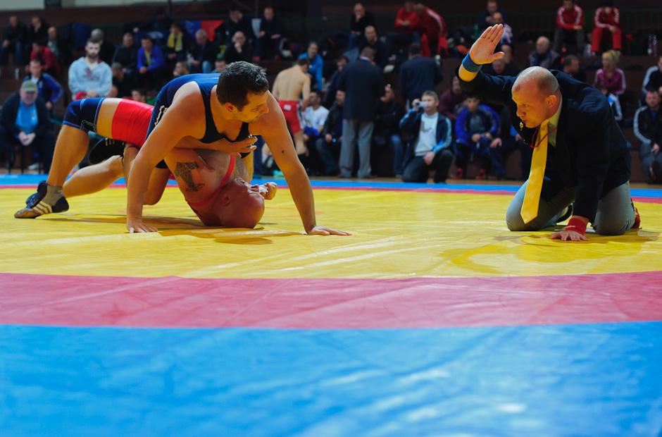 Zápasníci pod prísnym dozorom rozhodcu počas Majstrovstiev Slovenskej republiky v zápasení seniorov voľným štýlom 2011, Bratislava, Sobota 12.11.2011